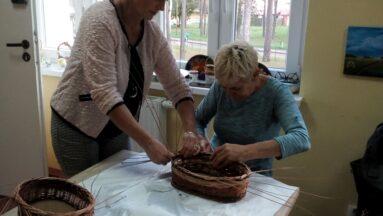 Dwie uczestniczki projektu wyplatają kosze z wikliny.