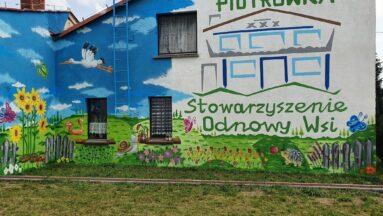 Mural kwiatowy wraz z logo Stowarzyszenia Odnowy Wsi Piotrówka.